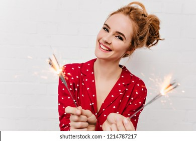 Close-up shot of positive girl wears funny pyjamas in new year morning. Winsome european woman holding sparklers and laughing on white background.