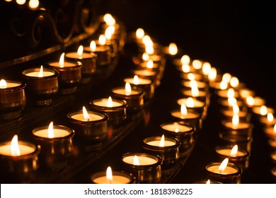 Close-up shot of prayer candles the darkness in a church. Small wax lighted candles as symbol of faith, christianity and peace.