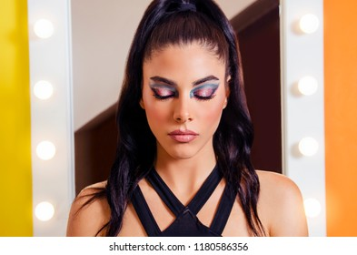Closeup shot of pretty girl with artistic makeup on with eyes closed ; makeup mirror in background