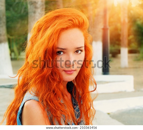 Closeup shot of a pretty red haired women in calm state looking at camera crossprocessed colors