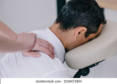 close-up shot of professional masseuse doing seated massage for businessman