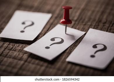 Nahaufnahme von Fragezeichen-Papier auf Holzhintergrund.