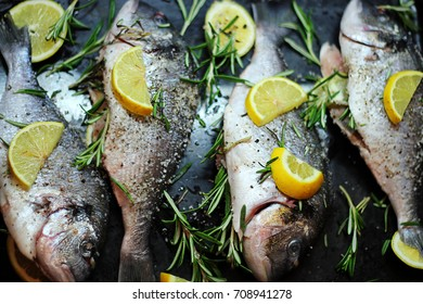 Close-up shot of raw fish with lemon ready for cooking. Sparus aurata. Concept of healthy food. Recipe of gilt-head bream fish.