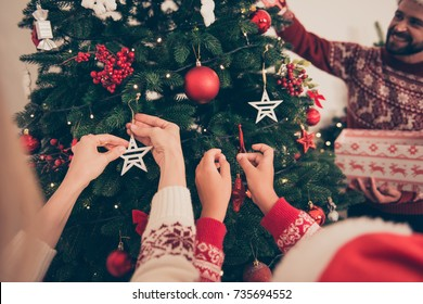 Closeup shot of relatives at home in knitted traditional costumes, ready to celebrate x mas eve. Happiness, friendship, parenthood, childhood, upbringing, unity, help, mother, father