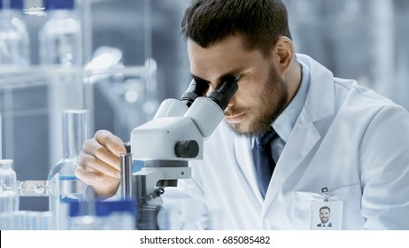 Close-up Shot of Research Scientist Adjusts His Microscope. He's Working in a High-End Modern Laboratory with Beakers, Glassware, Microscope and Working Monitors Surround Him.