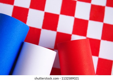 Close-up shot of rolls of paper, blue, white, and red placed over a checkered pattern paper on a white background. The image giving senses of colorfulness and the flags of France and Croatia.