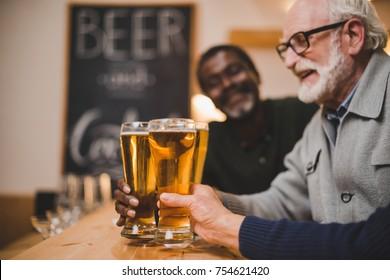 close-up shot of senior friends clinking beer glasses at bar counter