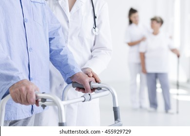 Closeup shot of a senior walking with walker assisted by a nurse