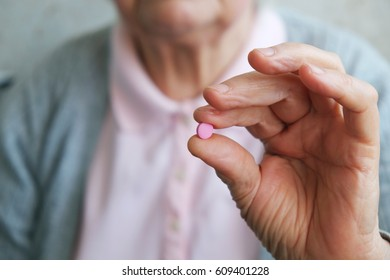 Closeup shot of a senior woman showing pink pill. Healthcare old people concept.