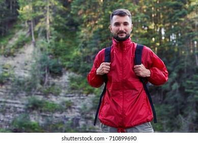 Close-up shot of serious bearded hiker looking at camera. Man posing at camera in mountains