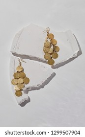 A closeup shot of a set of golden dangle earrings with coins. The set is isolated against the white textured platform against white background. Charming accessory for important occasion or party.