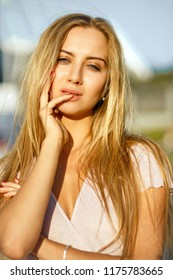 Closeup shot of sexy blonde woman with perfect skin and nude makeup posing at the avenue