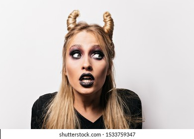 Close-up shot of shocked pretty witch. Interested blonde woman posing at halloween carnival.