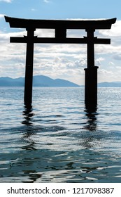 "Close-up shot of the silhouette of the less-known ""floating"" torii gate of Shirahige Shrine in Lake Biwa near Shiga Prefecture's Takashima City in portrait view."