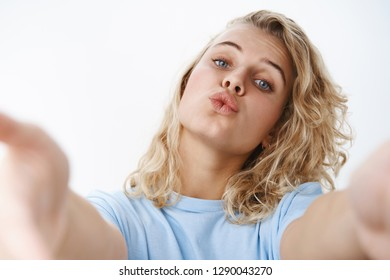 Close-up shot of silly and feminine carefree blond with blue eyes in t-shirt folding lips in kiss pulling hands towards camera as if holding it, wanting give mwah in sensual and flirty mood