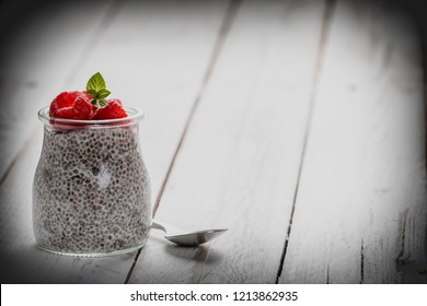 Closeup shot of small glass with sweet chia seeds pudding topped with fresh raspberry on white wooden table