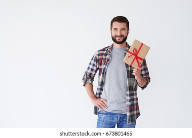 Close-up shot of smiling casual man holding present box in hands isolated over white background. Copy space