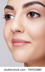Closeup shot of smiling happy female face with day makeup eyes shadows