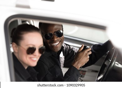 close-up shot of smiling police officers sitting in police car