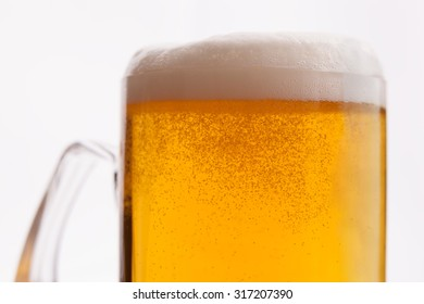 Closeup shot of sparkling light beer on isolated background
