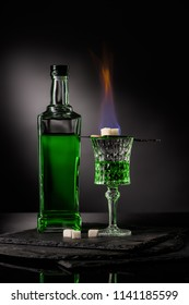 close-up shot of spoon with sugar cubes over burning absinthe in glass on dark background