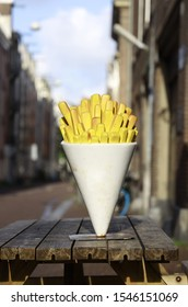 A closeup shot of a statue of french fries in a white cone on a wooden chair with blurred background