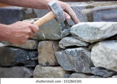 Close-up shot of a stonemason building a dry stone wall.