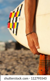 closeup shot of a surfer holding a surfboard at the beach