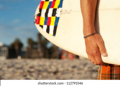 closeup shot of a surfer holding a surfboard at the beach