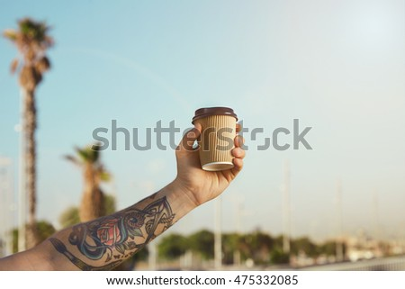 fe2cdc562 Closeup shot of a tattooed man's arm and hand with a corrugated cardboard  beige disposable coffee