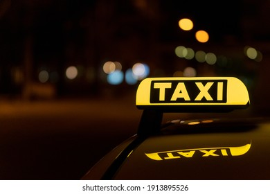 A close-up shot of a taxi sign in the night with bokeh lights in the background