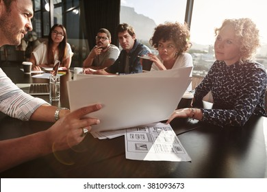 Closeup shot of team of young people going over paperwork. Creative people meeting at restaurant table. Focus on hands and documents.