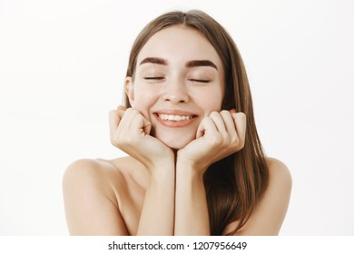 Close-up shot of tender dreamy and feminine pretty woman with brown hair leaning head on hands with closed eyes and sweet delighted smile recalling or imaging nice moment over gray background