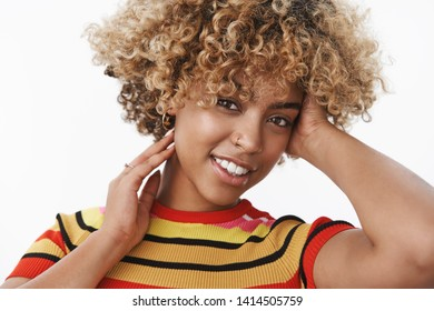 Close-up shot of tender and sensual attractive gentle african american stylish woman with fair afro haircut and pierced nose tilting head flirty and gently touching hair smiling at camera