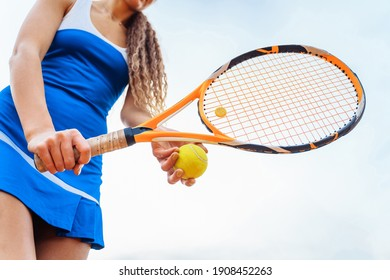 A close-up shot of a tennis ball and racket. The tennis player prepares to serve during the match. A beautiful sport that requires physical, emotional and mental preparation. Selective focus