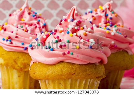 A close-up shot of three cupcakes on pink covered in sprinkles and icing.