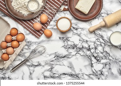 Close-up shot. Top view of a baking ingredients and kitchenware on the marble table background.