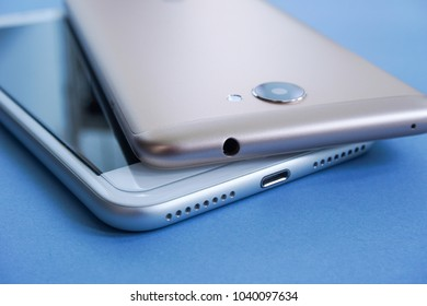 Closeup Shot of Two Different Earphones Audio Out Port of Smartphones on Blue Background