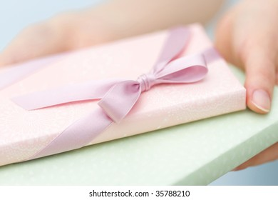 Close-up shot of two lovely gift boxes with woman's hands