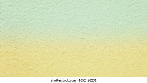 Close-up shot of two tones pastel colors, yellow and green cement wall blur mode. An abstract of light yellow and green wall for decorative and design.