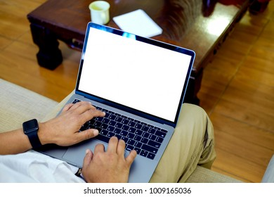 Closeup shot of an unidentifiable man using a laptop at home office.