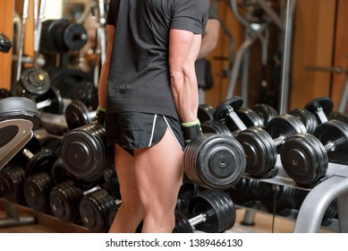 Closeup shot of unidentifiable muscular male picking up heavy dumbbell weights from equipment rack in modern gym .