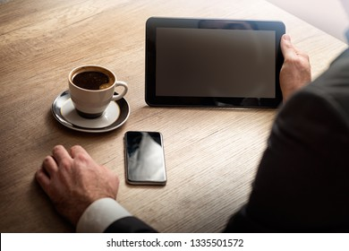 Close-up shot of an unrecognizable businessman using a digital tablet in an office