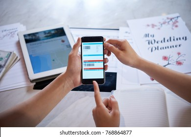Close-up shot of unrecognizable couple sitting at table and planning their honeymoon trip to exotic place, they holding smartphone in hands while booking hotel