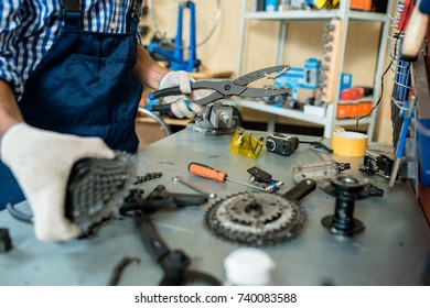 Close-up shot of unrecognizable mechanic wearing overall and checked shirt standing at desk covered with working tools and bicycle details