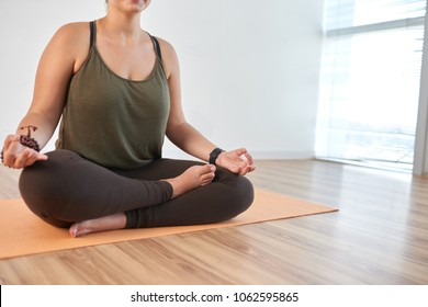 Close-up shot of unrecognizable young woman sitting in lotus position and meditating while having training at modern health club
