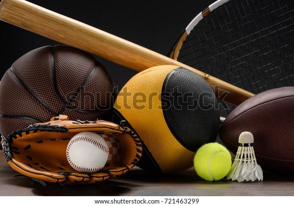 Closeup shot of various sports equipment, balls, baseball bat and shuttlecock on wooden surface