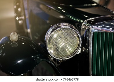 Closeup shot of vintage luxury green car front headlight. Antique vehicle decorating hobby for rich guy.