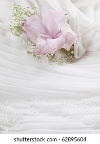 closeup shot of wedding dress with pink flower on it