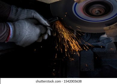 A close-up shot of a welder is busy in a coarse metal workpiece, grinding the apron with a rotating tool in the workshop.